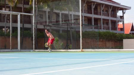 latino americana : Handosme man with an open-chested playing tennis at the court on tropical island. Video