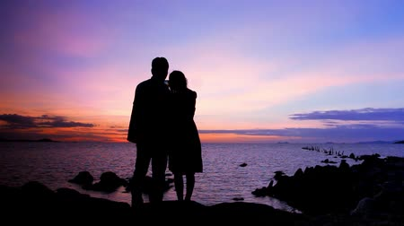 öykü : Silhouette couple in love taking self-portrait on the phone against amazing sunset. Video