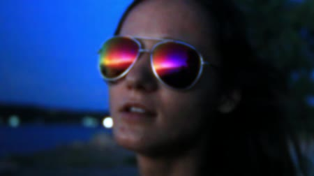 yansıma : Girl near beach looks at sea, take pictures on phone and her glasses reflected beautiful sunset Stok Video