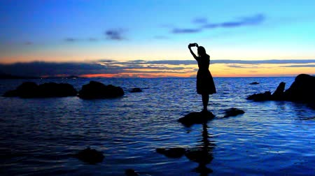 alma : Silhouette of young woman walks on the sea to stone and photographs amazing sunset On beach. Koh Samui, Thailand Stok Video