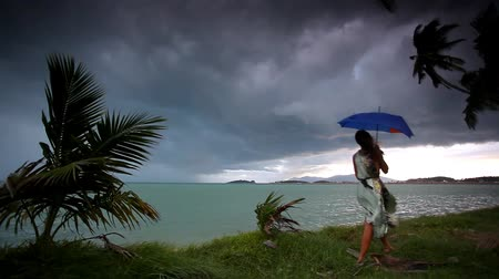 andar : young woman on a tropical beach with umbrella in rainy season. Video Koh Samui Vídeos