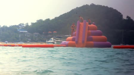 slayt : Friend dive with inflatable slides into the sea on Koh Samui Stok Video