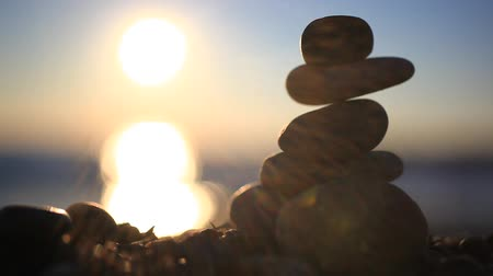 баланс : Stones pyramid on beach symbolizing zen, harmony, balance. Blurred Sea at sunset with bokeh background and reflected sun in water. Sound of the Sea