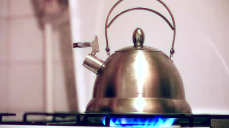 comutar : Tea kettle with boiling water on gas stove