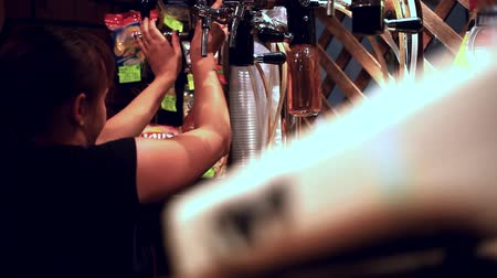rascunho : Female bartender pours the beer into a bottles