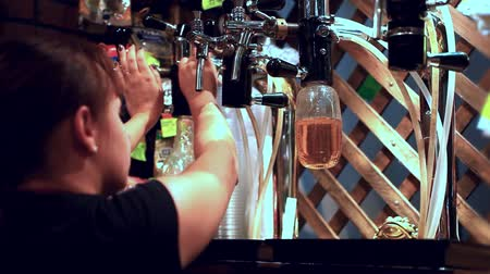 taberna : Female bartender pours the beer into a bottles