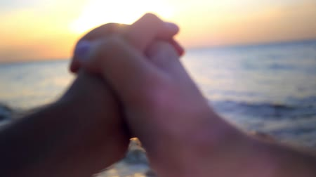 holding : Couple in love holding hands at sunset in the beach Stock Footage