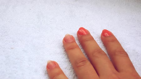lakier do paznokci : Manicure - Beautiful manicured womans nails with pink nail polish on soft white towel.