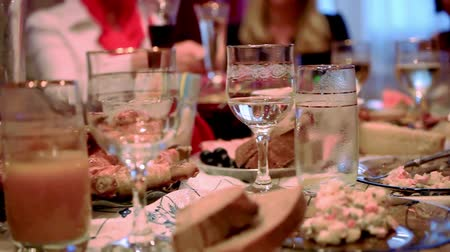 setting : Luxury banquet table setting at restaurant. Blurred background with bokeh. Set service with silverware, refreshments and glass. People eating
