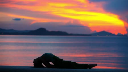 традиционный : girl practicing yoga, doing exercises lying on the background of beautiful sunset