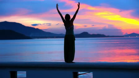 aktywność : Beautiful sunset and young woman rising her hands into air.