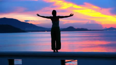 emocional : Beautiful sunset and young woman rising her hands into air.