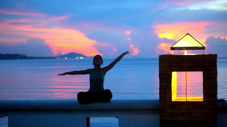 meditação : Young woman doing yoga and meditates over the sunset background.