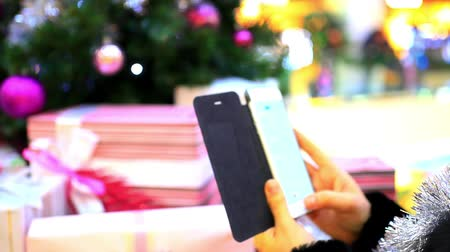 dekoracje : Womans Hand uses phone and taking photo of Christmas tree by smartphone Wideo