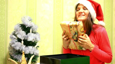 pulóver : Happy young woman in winter hat open box gift near christmas tree