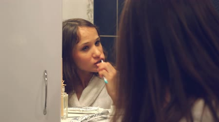 dış : Young pretty woman brushing teeth in front of the mirror