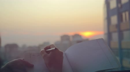 autor : female hands with pen writing on notebook  at sunset in the city Vídeos