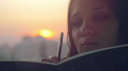 připomínka : Young beautiful woman making some important notes on notebook at sunset in the city Dostupné videozáznamy