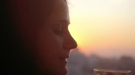 herbata : Slow motion of beautiful girl drinking coffee by the window at silhouette Of sunset City Wideo