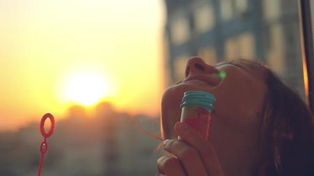 разнообразие : Slow motion of smiles young beautiful happy woman blowing bubble at sunset city