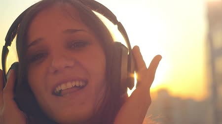 garça real : Slow motion of Young woman get dressed headphones listening to music  at city sunset and dancing