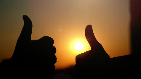 subir : Slow motion of female and male hands showing a thumb up gesture at city sunset