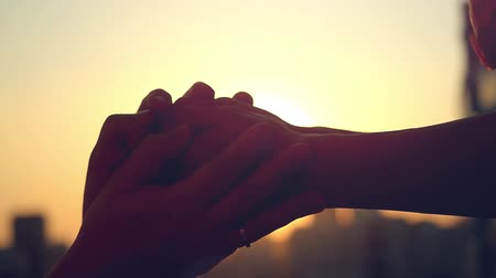 detém : Slow motion of people in love holding hands at sunset on blurred silhouette of the city