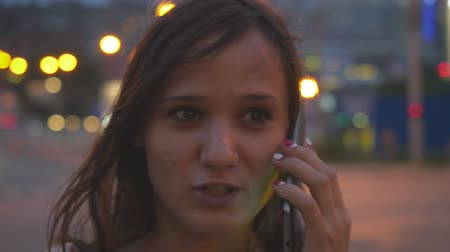urge : Smiles beautiful businesswoman talking by mobile phone in city at night street