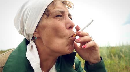 başörtüsü : aged woman smoking a cigarette in a scarf on the nature and coughs