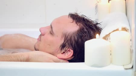 wanna : Young Man lies in the bath Washing Hair Head and relaxing. Candles burning on background