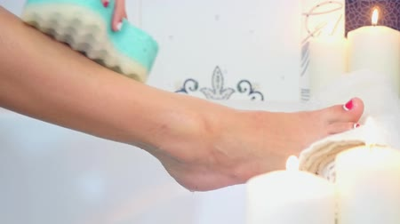 gąbka : sexy woman washing legs in bath with blue sponge on burning candle background Wideo