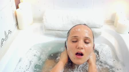 wanna : Young beautiful woman relaxing in a bath, washing herself hair