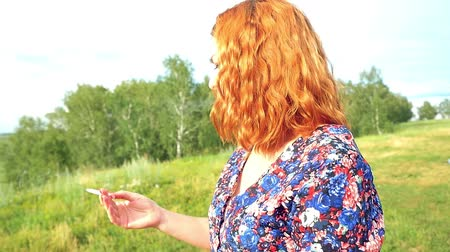 rocks red : young curly red-haired woman smokes cigarette on the nature