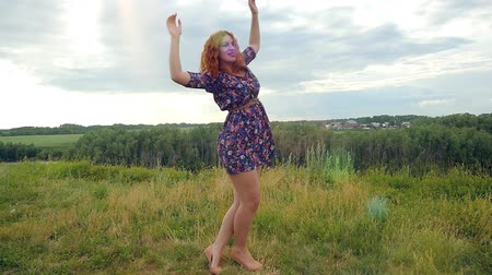 giydirmek : Young curly red-haired woman dancing happy in summer meadow. dragonfly flying on background Stok Video
