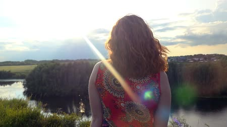 стоять : Young red-haired curly haired woman enjoys  landscape standing on a mountain looks at sun  in feeling happiness and freedom