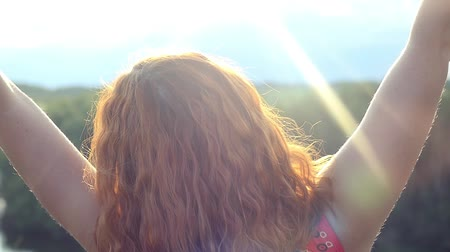 braços levantados : Young red-haired curly haired woman standing on rock looks at sun and raising hands in feeling happiness