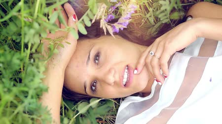 луг : young cute summer brunette girl lying on a flower meadow relaxing smiling and smelling the flowers thoughtfully