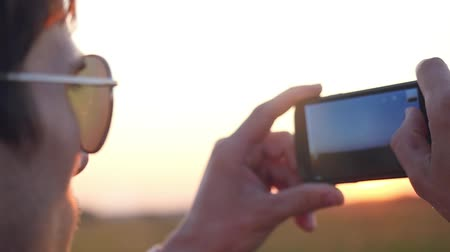 мобильный телефон : Handsome young man in sunglasses holds cell mobile phone take photo of wheat field on the sunset sky  in rural meadow