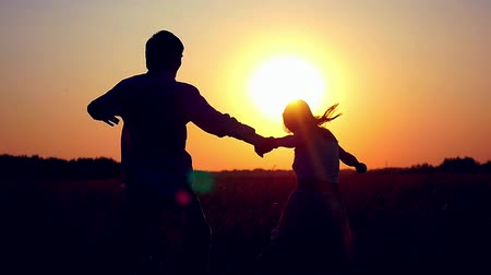 boldogság : Silhouette of happy couple join hands runs across the field in sunset light and cuddling, lifestyle - happiness Stock mozgókép