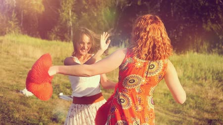 szeplők : Two beautiful girl friends pillow fight on nature in sunset time