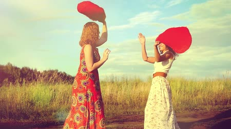 kıvırcık saçlar : Two beautiful girl friends pillow fight on nature in sunset time