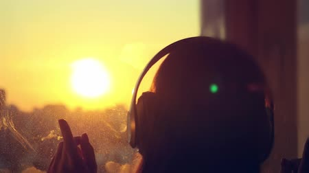 наушники : Attractive young woman wears headphones listening to music on the music player at blurred city background. enjoying the tunes in slowmotion at sunset