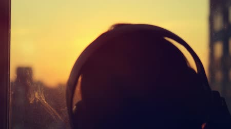 paylaşımı : Attractive young woman wears listening to music on the music player at city blurred background with sunset. enjoying the tunes in her headphones in slowmotion