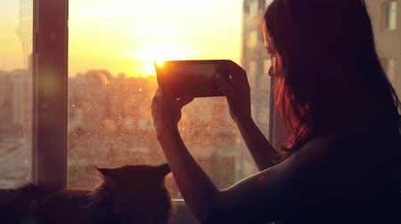 fur headphones : Young woman in headphones relaxing with her lovely Maine Coon cat at window taken pictures of blurred city background at sunset in slowmotion
