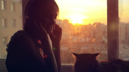 coon : Young woman in headphones relaxing with her lovely Maine Coon cat at window with blurred city background at sunset in slowmotion Stock Footage