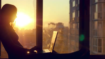 setting : Beautiful young brunette business woman working on her laptop during sunset. Girl sitting on the window at modern building blurred background in city Stock Footage
