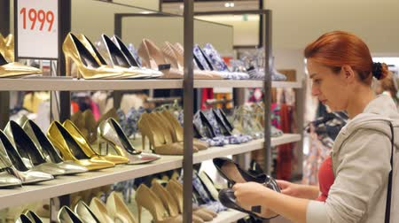 high heels : Young red-haired woman choosing shoes in a shoe store