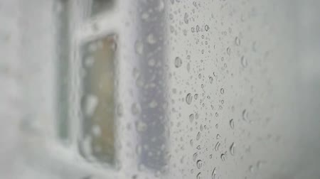 nzl : Urban view of rain drops falls on a window during a stormy day overlooking city skyline in the background