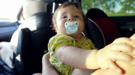 necessity : Laughing little baby with nipple in the car in slowmotion