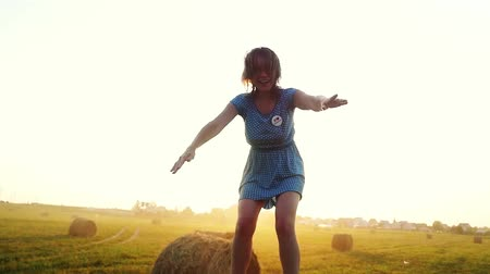 szénaboglya : Young woman having fun on the field jumping up on straw roll in slowmotion during sunset